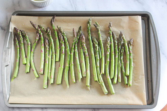 raw asparagus on a baking sheet lined with parchment paper
