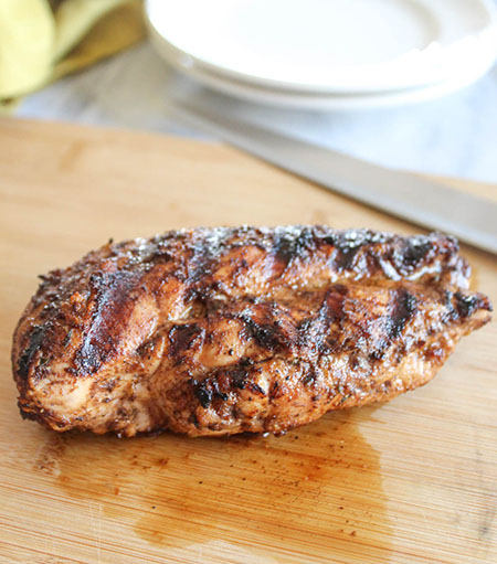 a grilled chicken breast on a cutting board