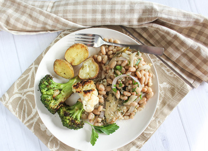 An overhead view of garlic herb chicken with white beans on a plate with broccoli and cauliflower
