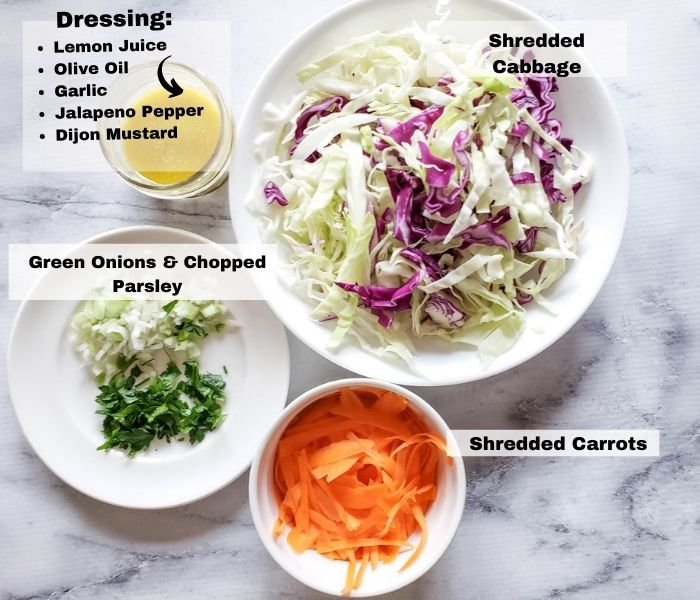 an overhead view of the ingredients: chopped onions & parsley, Shredded carrots, shredded cabbage, dressing