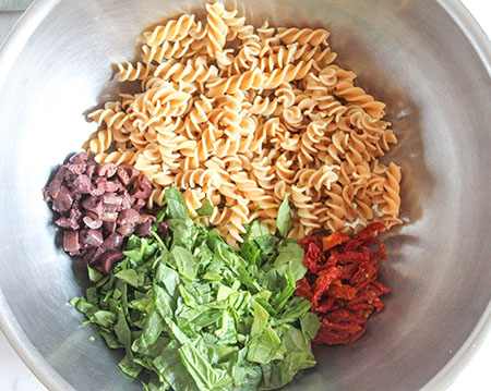 The pasta salad ingredients in a mixing bowl: chopped spinach, olives, sun-dried tomatoes and pasta