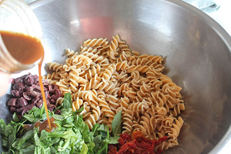 dressing pouring over the pasta salad