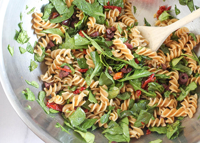Spinach pasta salad all mixed together in a mixing bowl.