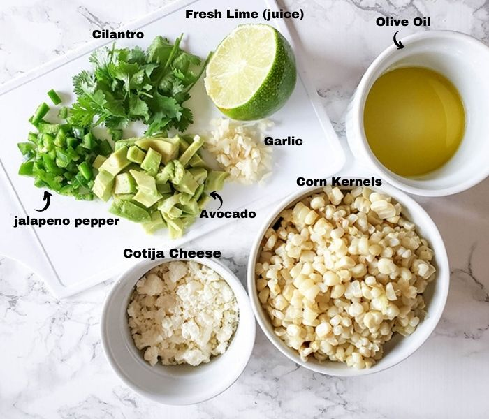 the ingredients for corn salad, cotja cheese, diced avocado, jalapeno pepper, cilantro, lime juice, olive oil garlic and corn kernels