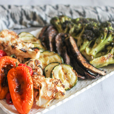 A close up picture of grilled peppers, cauliflower, zucchini, mushrooms and broccoli on a platter