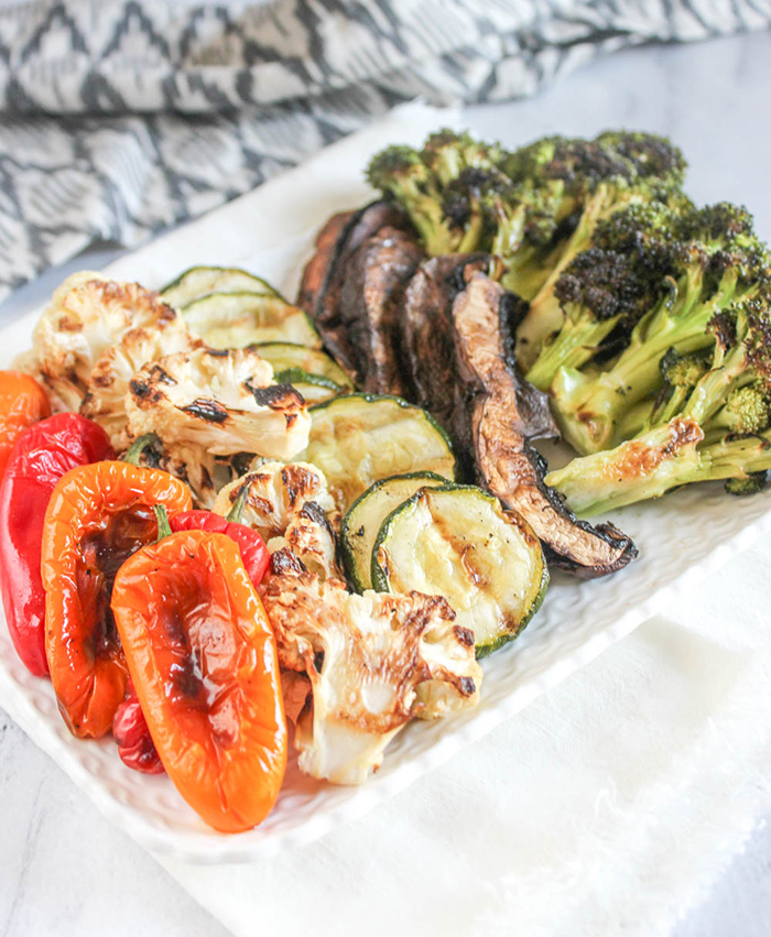 A plate of assorted grilled vegetables: peppers, cauliflower, zucchini, mushrooms and broccoli