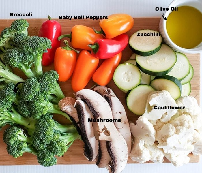 an overhead view of raw vegetables: broccoli, cauliflower, mushrooms, peppers zucchini and olive oil