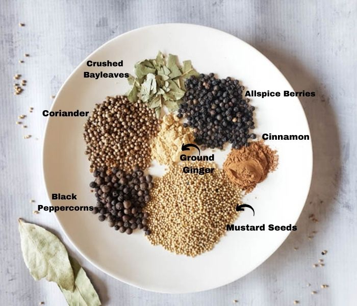a picture of the pickle spice ingredients on a plate: mustard seeds, peppercorns, coriander, ginger, cinnamon, crushed bayleaves on a plate