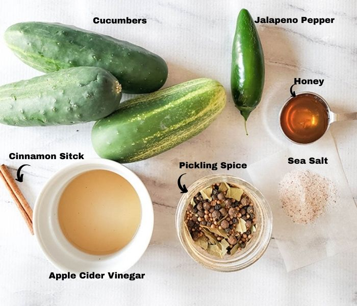 an overhead view of the ingredients for sweet and spicy pickles: pickling spice, apple cider vinegar, salt, honey, jalapeno peppers, cucumbers and cinnamon stick