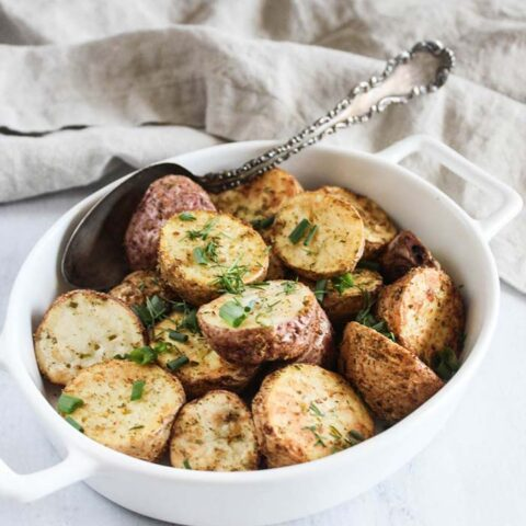 a bowl of air fryer potatoes with a spoon