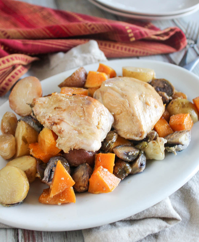 two chicken breasts on top of roasted vegetables on a white platter