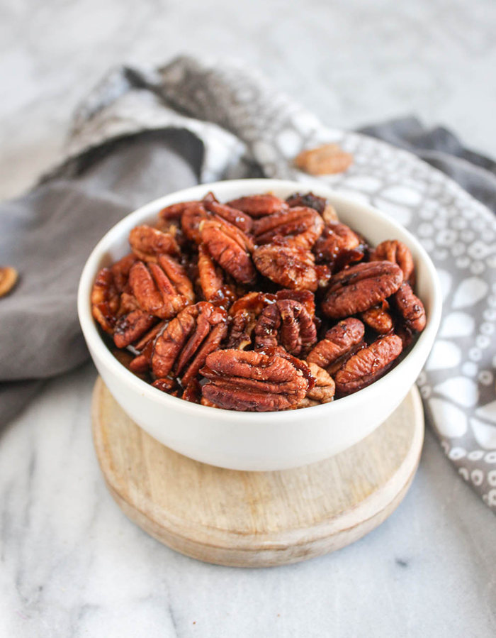 A white bowl filled with sweet and spicy pecans.