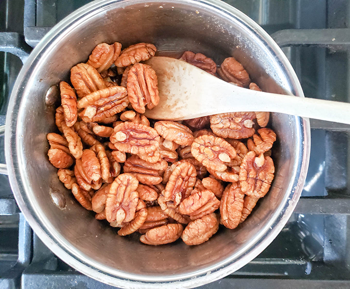 An overhead view of pecans in a saucepan with a spoon.