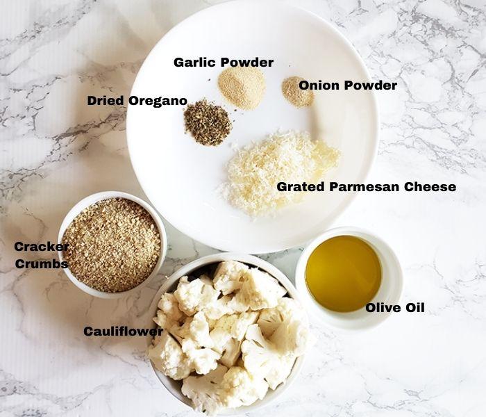 a photo of ingredients: cauliflower, cracker crumbs, dried oregano, garlic powder, onion powder, grated parmesan cheese, olive oil