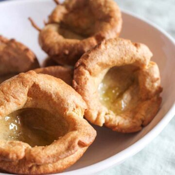 a close up shot of yorkshire puddings in a white dish
